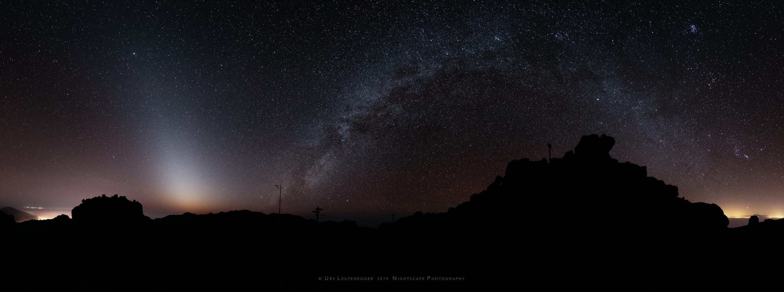 Zodiacal light with Milky Way over silhouette of Pico de la Cruz, La Palma. Light pollution from Los Llanos de Aridane and Tenerife at horizon.