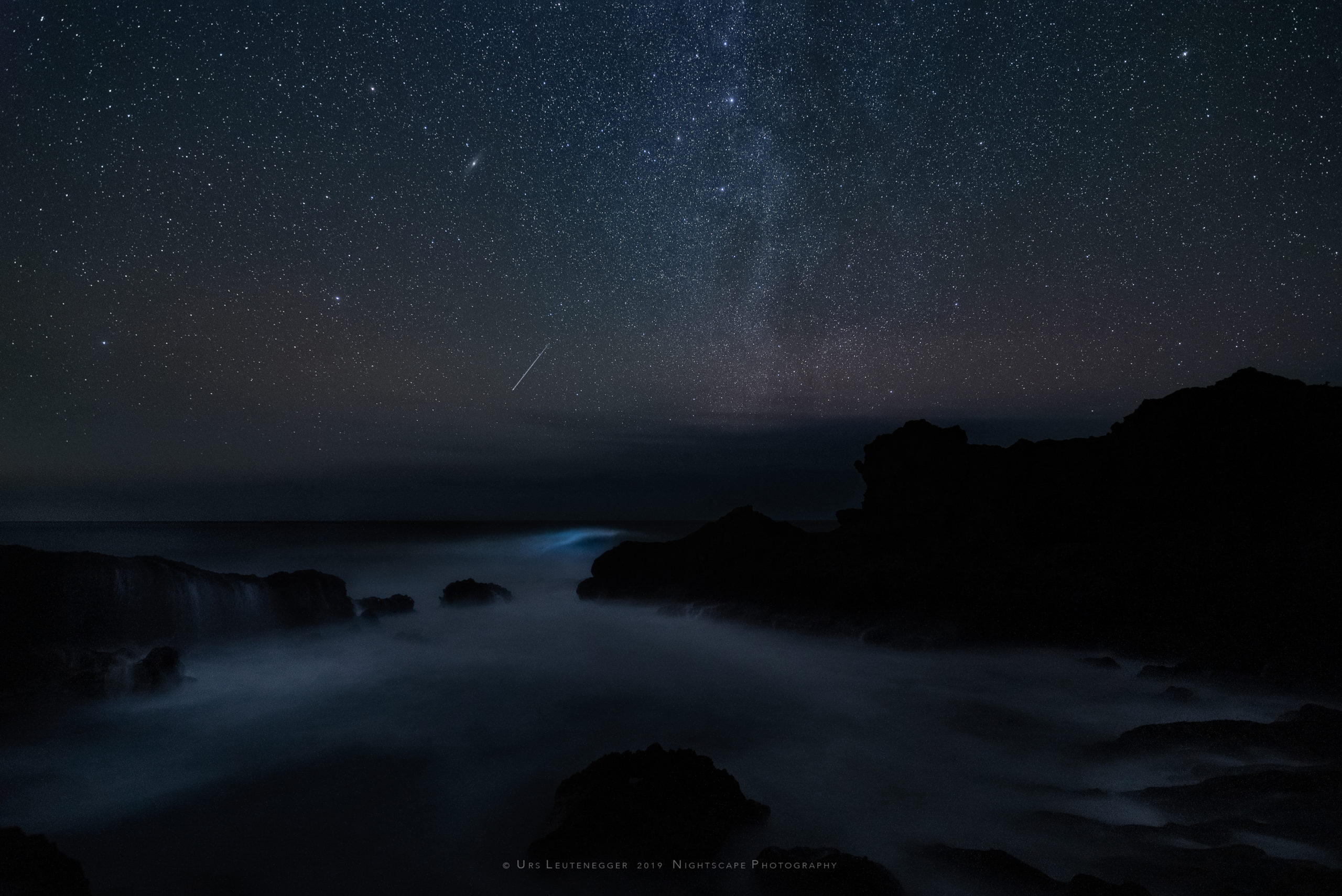 Vertical Milky way over Atlantic Ocean, Cassiopeia and Andromeda, bioluminescence in sea wave, single meteor hitting atmosphere close to horizon. Natural night sky glow. Northwest of La Palma.