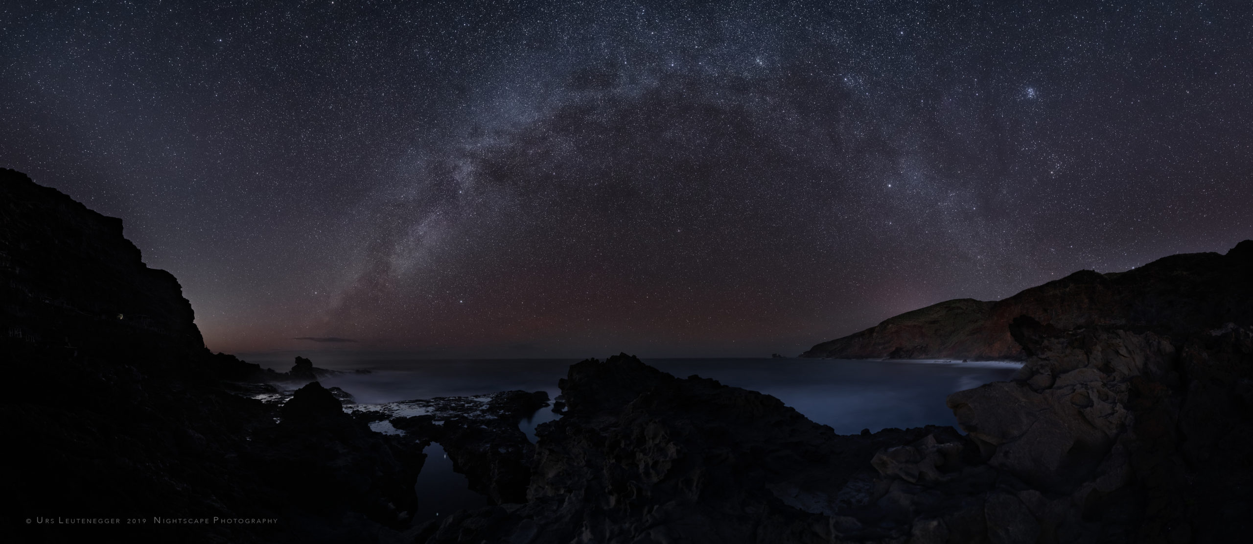 Milky Way over low tide northwest-coast of La Palma. Mirrored stars Vega and Deneb in the sea, Lyra and Swan, Cassiopeia and Pleiades and Hyades in the sky. Zodiacal partly light behind coastal silhouette.